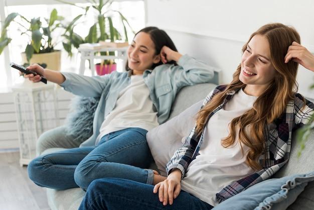 Fröhliche junge frauen, die fernsehen Kostenlose Fotos