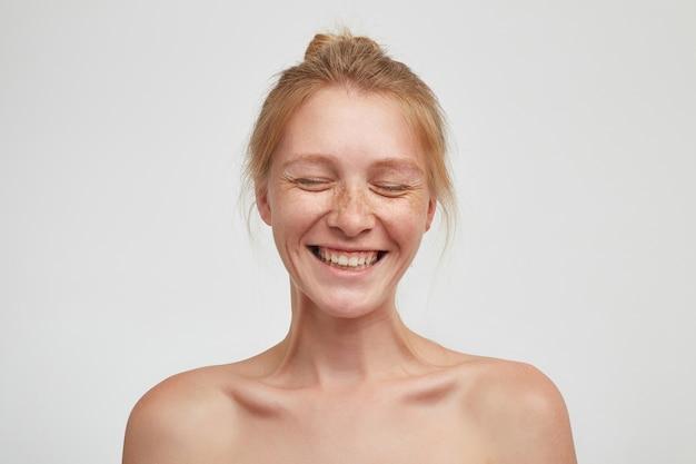 Fröhliche junge gut aussehende rothaarige dame mit brötchenfrisur, die glücklich mit geschlossenen augen lacht und ihre angenehmen gefühle zeigt, während sie über weißem hintergrund aufwirft Kostenlose Fotos