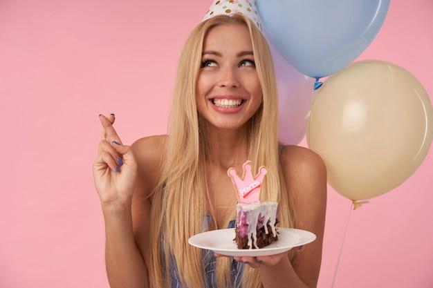Fröhliche junge langhaarige frau mit langen blonden haaren, die finger kreuzen, während sie sich an ihrem geburtstag wünschen und ein stück kuchen mit kerze über mehrfarbigen luftballons und rosa hintergrund halten Kostenlose Fotos