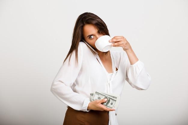 Fröhliche modefrau, trinke kaffee, halte geld und telefoniere Kostenlose Fotos