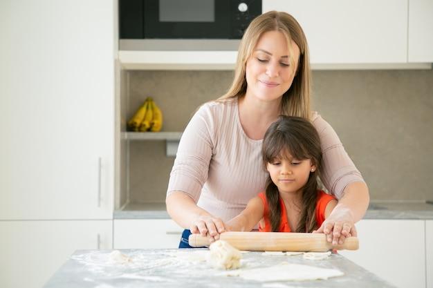 Fröhliche mutter und ihr mädchen kochen zusammen und rollen teig auf küchentisch mit mehlpulver. Kostenlose Fotos