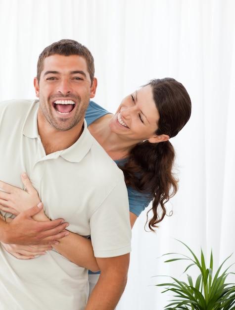 Fröhliche paare, die zusammen im wohnzimmer lachen Premium Fotos