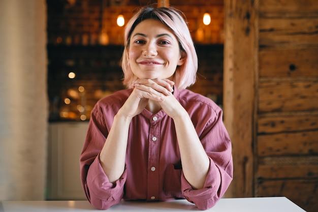 Fröhliche positive junge frau mit rosafarbenem haar, das zu hause vor goldenem hellem hintergrund sitzt und optimistischen glücklichen gesichtsausdruck hat, hände unter kinn hält und breit in die kamera lächelt Kostenlose Fotos