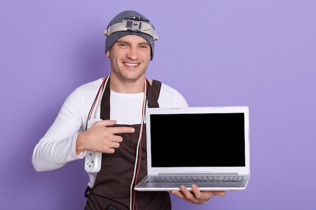 Fröhliche positive radiomanin hält laptop mit leerem bildschirm, macht geste, zeigt mit zeigefinger, hat doppeladapter und verschiedene schnüre am hals, steht mit notwendiger ausrüstung. Kostenlose Fotos