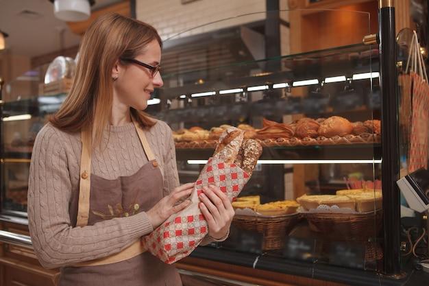 Fröhliche professionelle bäckerin, die frisches leckeres brot hält und in ihrer bäckerei arbeitet Premium Fotos