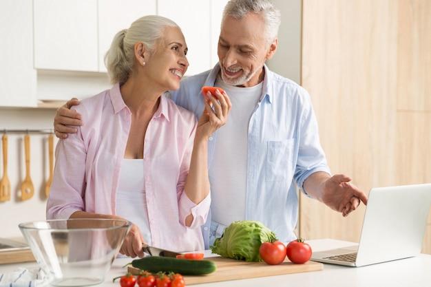 Fröhliche reife liebespaarfamilie mit laptop und kochen Kostenlose Fotos