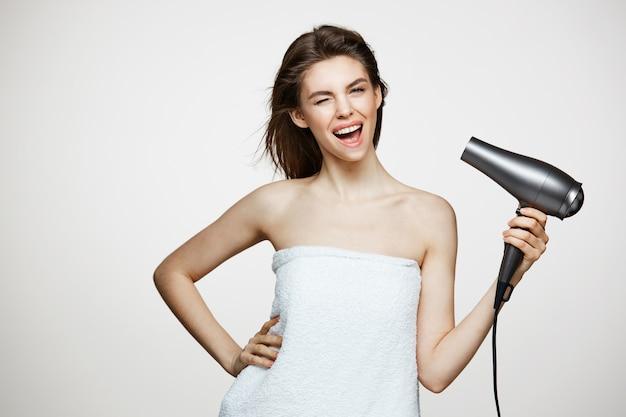 Fröhliche schöne frau im handtuch lächelnd lachend singend mit fön, der lustiges gesicht macht. beauty spa und kosmetologie. Kostenlose Fotos