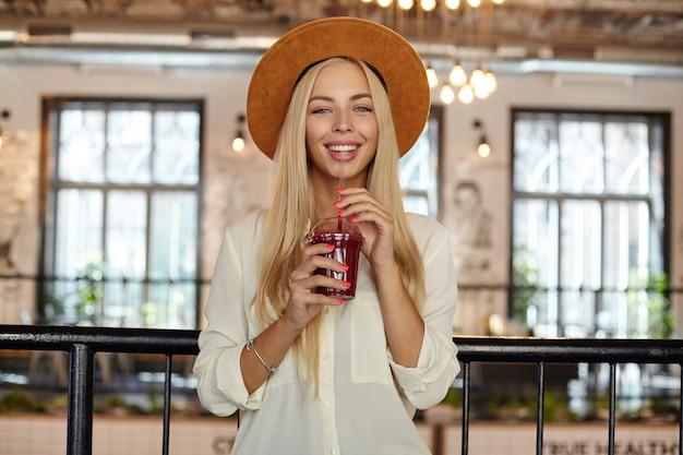Fröhliche schöne junge frau mit langen blonden haaren, die glücklich schauen, während sie über caféinnenraum aufwerfen und tasse limonade in händen halten Kostenlose Fotos