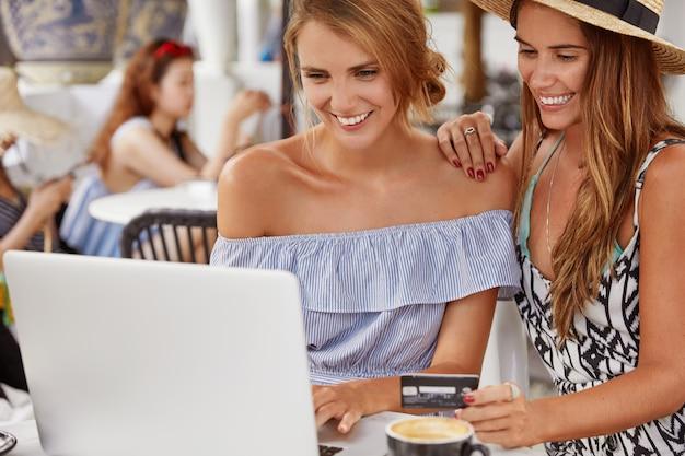 Fröhliche studentinnen machen projekt auf laptop-computer. lächelnde homosexuelle frauen surfen im internet in webstores, halten eine kreditkarte für online-zahlungen bereit und verwenden moderne elektronische geräte. online einkaufen. Kostenlose Fotos