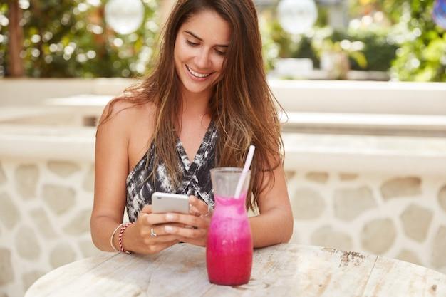 Fröhliche wunderschöne weibliche dame mit luxuriösem dunklem haar freut sich über benachrichtigung auf dem handy, sms-feedback, umgeben von frischem smoothie, genießt kostenlose internetverbindung im café Kostenlose Fotos