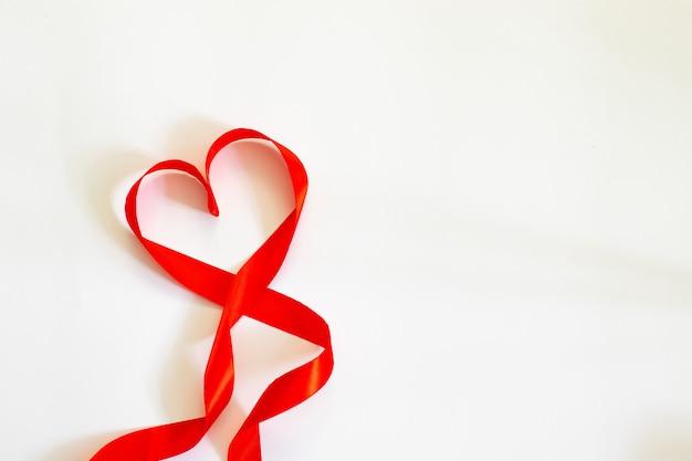 Fröhlichen valentinstag. rotes band-herz auf weißem hintergrund. Premium Fotos