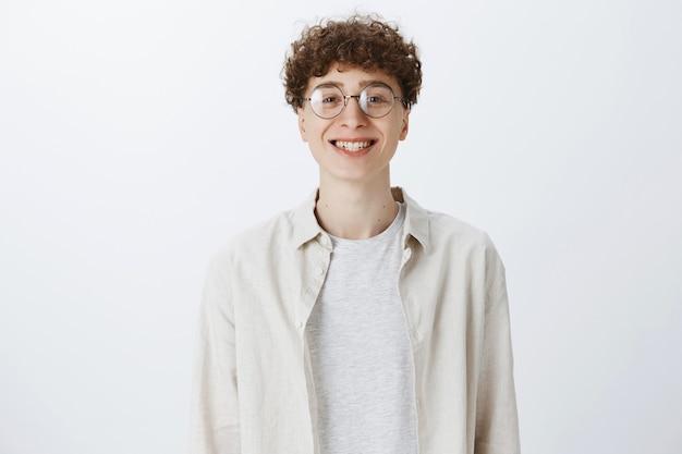 Fröhlicher attraktiver teenager, der gegen die weiße wand aufwirft Kostenlose Fotos