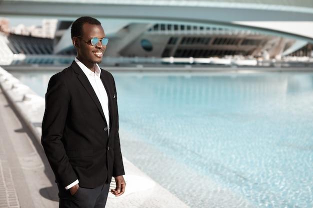 Fröhlicher glücklicher junger afroamerikanischer büroangestellter, der schwarzen eleganten anzug und stilvolle schatten trägt, die am städtischen brunnen stehen und hand in der tasche halten Kostenlose Fotos
