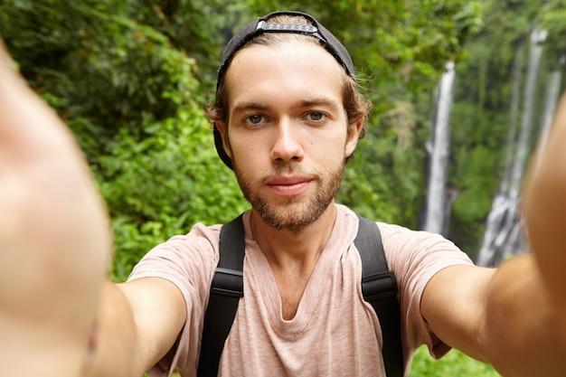 Fröhlicher junger bärtiger hipster, der baseballmütze trägt, die selfie in seinen exotischen ferien nimmt Kostenlose Fotos