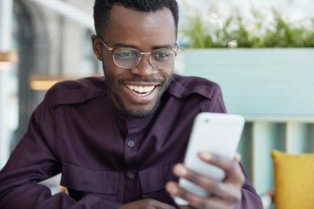 Fröhlicher junger geschäftsmann in runder brille und abendgarderobe, prüft newsfeed auf modernem smartphone, verbunden mit drahtlosem internet Kostenlose Fotos