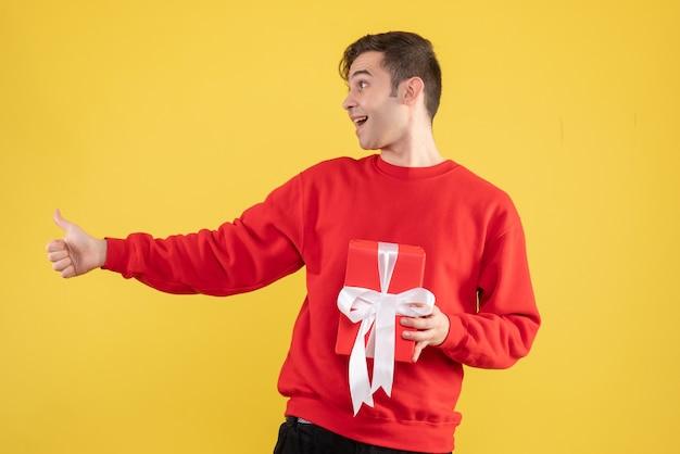 Fröhlicher junger mann der vorderansicht mit dem roten pullover, der daumen auf zeichen gelb macht Kostenlose Fotos