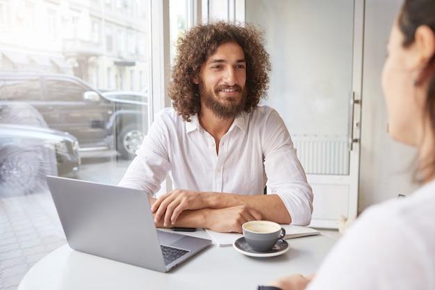 Fröhlicher junger mann mit bart und braunem lockigem haar, der freund im café trifft, entfernt mit modernem laptop arbeitet, am tisch nahe fenster mit verschränkten armen sitzt Kostenlose Fotos