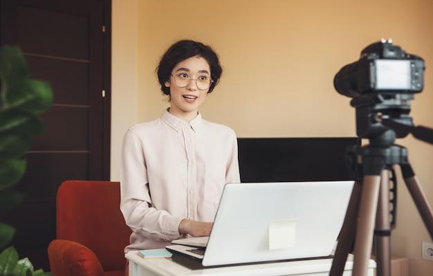 Fröhlicher kaukasischer student, der eine online-lektion während der quarantäne mit einem laptop und einer modernen kamera hat Premium Fotos