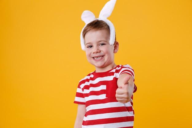 Fröhlicher kleiner junge, der hasenohren trägt und daumen hoch zeigt Kostenlose Fotos