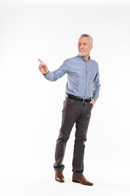 Fröhlicher mann, der mit der hand beiseite zeigt und isoliert lächelt Premium Fotos