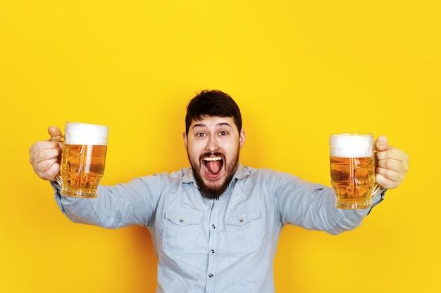 Fröhlicher mann mit zwei gläsern bier, bild über trendiger gelber wand Premium Fotos