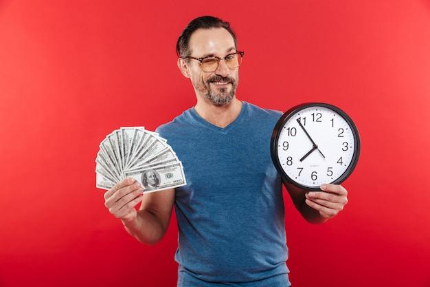 Fröhlicher positiver mann in der bunten sonnenbrille, die geld und uhr beim zwinkern hält. Premium Fotos