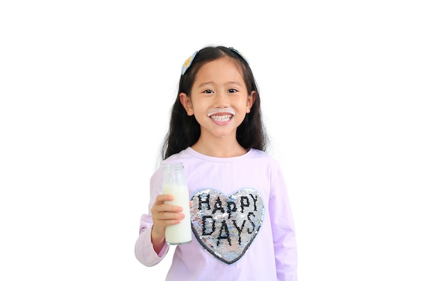Fröhliches asiatisches kleines kindermädchen, das milch von der glasflasche trennt, lokalisiert auf weißem hintergrund. Premium Fotos