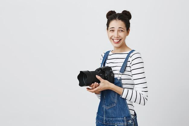 Fröhliches glückliches hipster-mädchen, das fotos macht, lacht und kamera benutzt, fotografiert Kostenlose Fotos