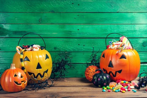 Fröhliches halloween! kürbis mit süßigkeit im haus. Premium Fotos