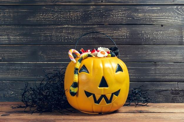 Fröhliches halloween! kürbis mit süßigkeit im haus Premium Fotos