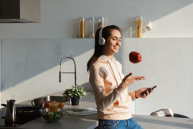 Fröhliches junges mädchen, das musik mit kopfhörern an der küche zu hause hört, einen apfel isst, handy hält Premium Fotos