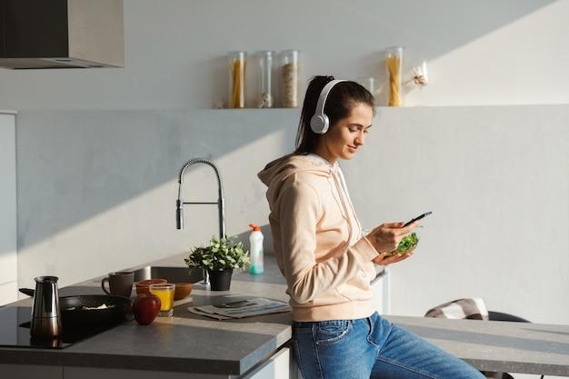Fröhliches junges mädchen, das musik mit kopfhörern an der küche zu hause hört und salat von einer schüssel isst Premium Fotos