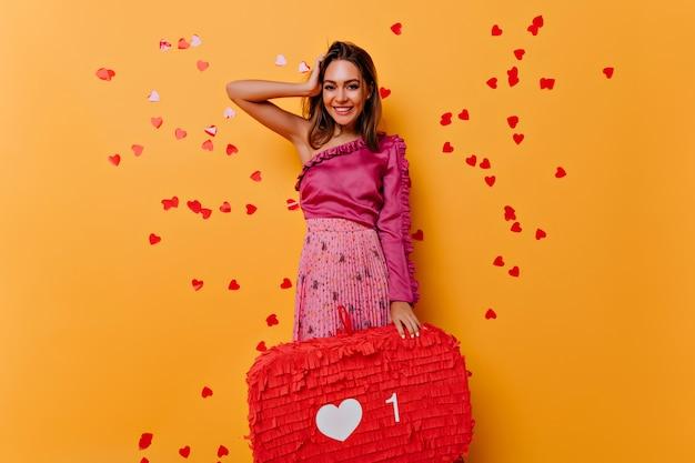 Fröhliches junges mädchen im rosa kleid, das soziale netzwerke genießt. porträt der entzückenden dame, die glück auf gelb ausdrückt. Kostenlose Fotos