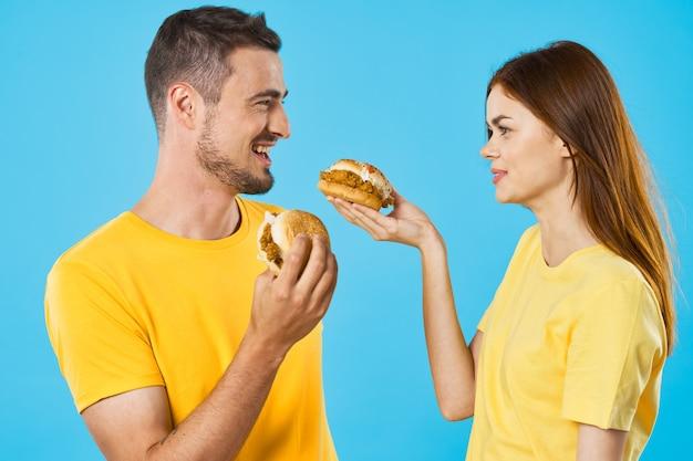 Fröhliches junges paar in gelben t-shirts mit hamburgern Premium Fotos