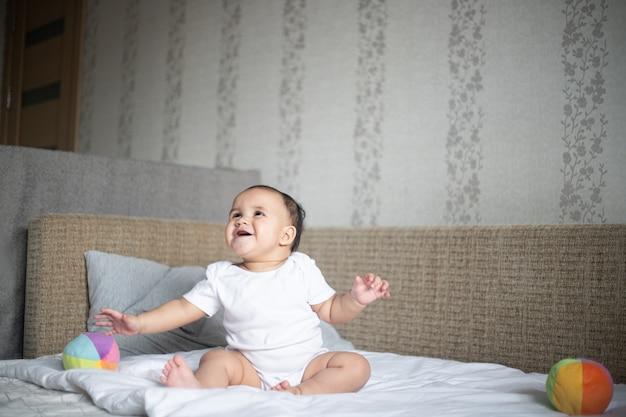 Fröhliches kleines baby, das auf einem bett gegen eine wand unter den lichtern in einem raum spielt Kostenlose Fotos