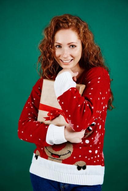 Fröhliches mädchen, das weihnachtsgeschenk umarmt Kostenlose Fotos