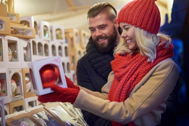 Fröhliches paar auf dem weihnachtsmarkt Kostenlose Fotos