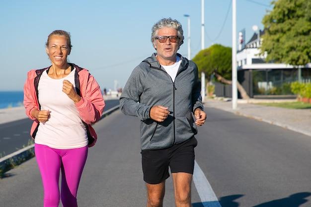 Fröhliches reifes paar, das entlang flussufer läuft. grauhaariger mann und frau, die sportkleidung tragen und draußen joggen. aktiver lebensstil und alterskonzept Kostenlose Fotos