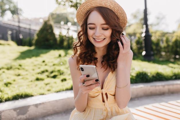 Fröhliches rothaariges mädchen im niedlichen hut las nachrichten mit glücklichem lächeln. foto im freien der liebenswerten ingwerfrau im gelben kleid, das im park am morgen entspannt. Kostenlose Fotos