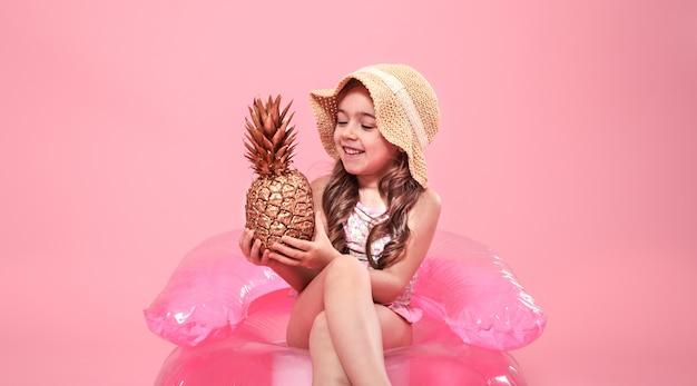 Fröhliches sommermädchen mit ananas auf farbigem hintergrund Kostenlose Fotos