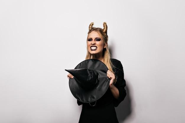 Fröhliches vampirmädchen, das in halloween aufwirft. emotionale junge hexe, die party genießt. Kostenlose Fotos