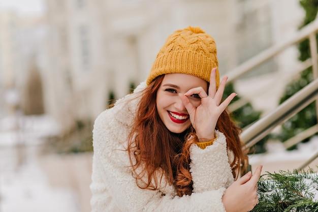 Fröhliches weibliches modell, das spaß im winter hat. erfreute kaukasische ingwerfrau, die über natur lacht. Kostenlose Fotos