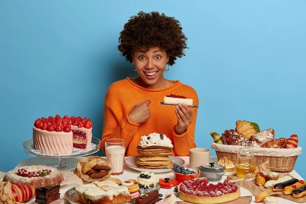 Froh, dass die dunkelhäutige frau positiv aussieht, auf sich selbst zeigt, ein leckeres stück kuchen in der hand hält und fragt, ob sie alles essen soll, gekleidet in einen orangefarbenen pullover, isoliert an der blauen wand. Kostenlose Fotos