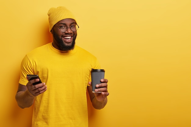 Froh, dass ein afroamerikaner nachrichten in sozialen netzwerken liest und ein heißes getränk aus einer einwegbecher genießt Kostenlose Fotos
