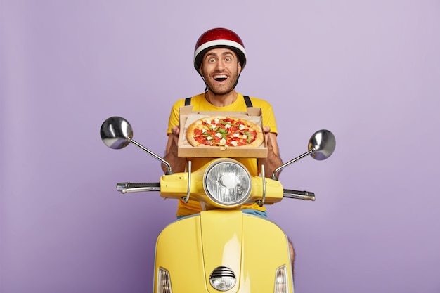 Froh, dass ein erfahrener lieferbote einen gelben roller fährt, während er die pizzaschachtel hält Kostenlose Fotos