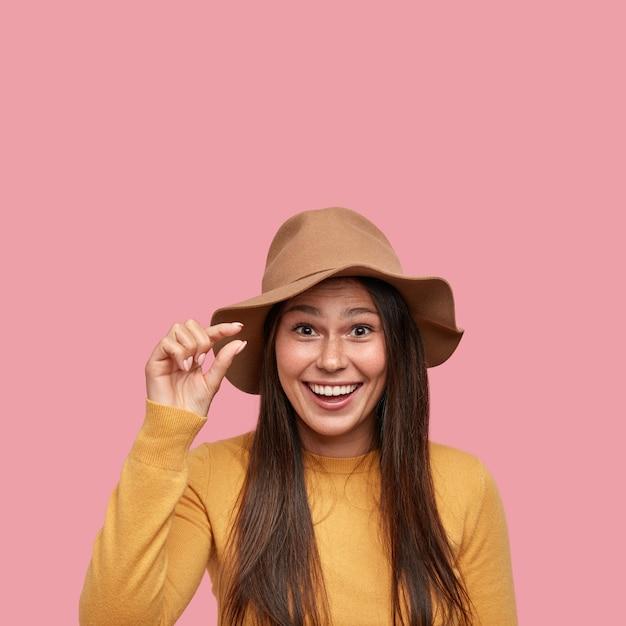 Froh, junger hipster formt winziges objekt mit dem finger, lächelt fröhlich, gut gelaunt Kostenlose Fotos