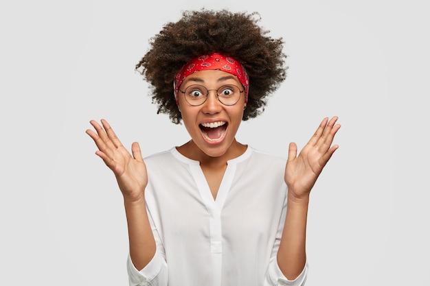 Froh überrascht, schöne junge afroamerikanerin gestikuliert aktiv und ruft laut aus, schockiert von niedrigem preis und verkauf, trägt stilvolles stirnband und bluse, isoliert über weißer wand. Kostenlose Fotos