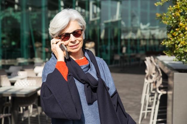 Frohe ältere dame, die gute nachrichten vom telefongespräch lernt Kostenlose Fotos