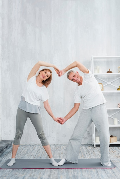 Frohe ältere paare, die herz mit ihren händen beim zu hause trainieren bilden Kostenlose Fotos
