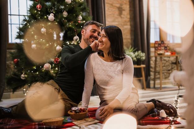 Frohe ältere paare mit lichtern und weihnachtsbaum hinten Kostenlose Fotos